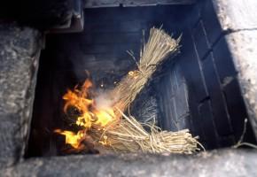 竈で藁を焼く